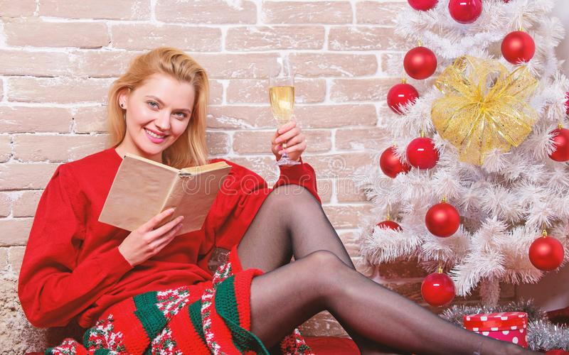 Woman happy smiling near christmas tree enjoy celebration. Noel and joy. Girl in red dress relaxing with glass of. Champagne near christmas tree. Waiting for stock photography