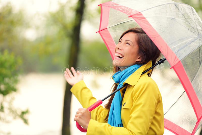 Woman happy with umbrella under the rain. During Autumn forest walk. Girl enjoying rainy fall day looking up at sky smiling cheerful. Mixed race Caucasian / stock images