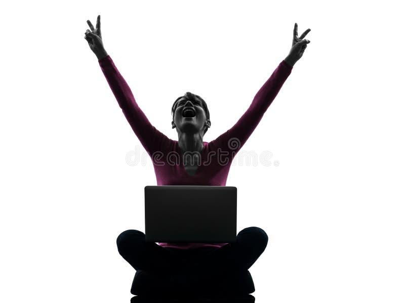 Woman happy winning computing laptop computer silhouette. One caucasian woman happy winning computing laptop computer in silhouette studio on white background royalty free stock image