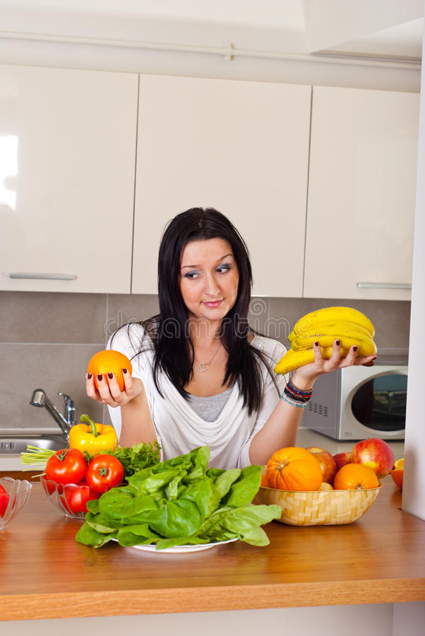 Woman hard choice orange or banana royalty free stock images