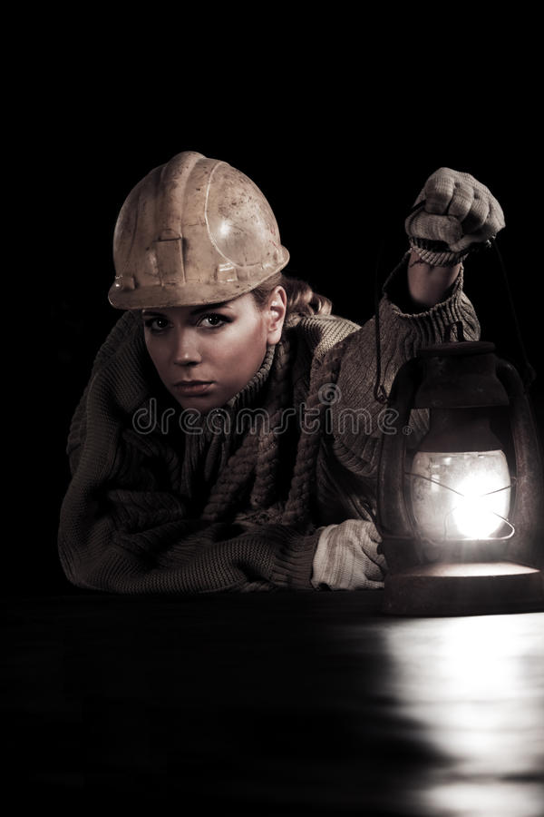 Woman in hardhat. Beautiful young woman in hardhat with oil stove royalty free stock image