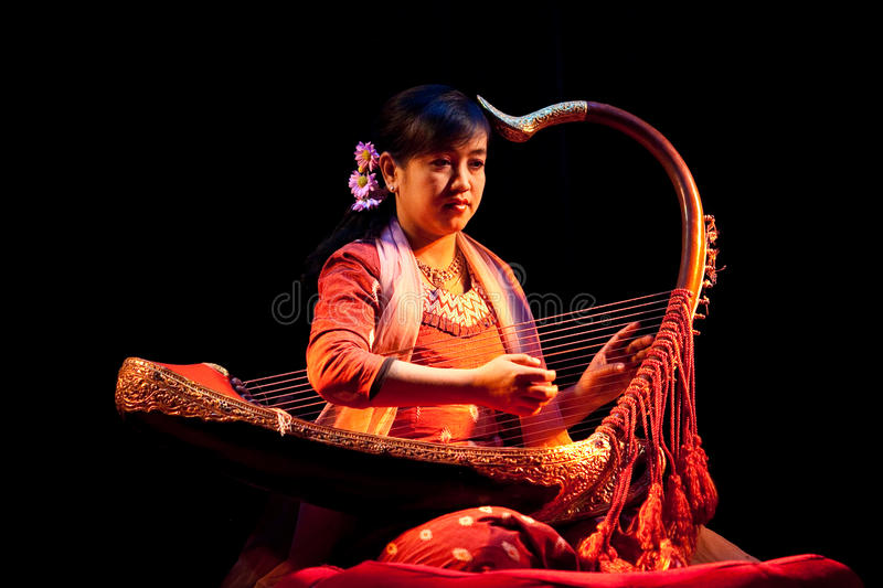 Woman with Harp, Myanmar. MANDALAY, MYANMAR - JANUARY 10: Woman musician with Harp plays on the evening show in honor of Karen New Year at Mandalay Marionette royalty free stock image