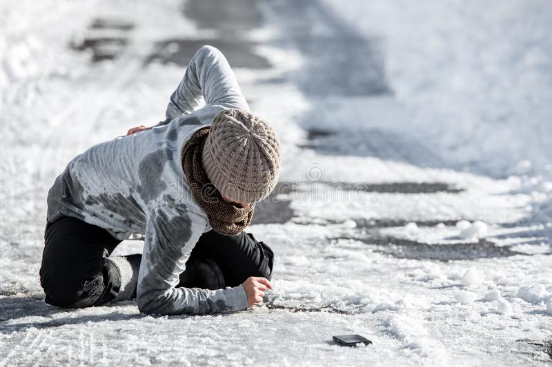 Woman has an accident cause of black ice on the road, downfall and injury. Copyspace royalty free stock images
