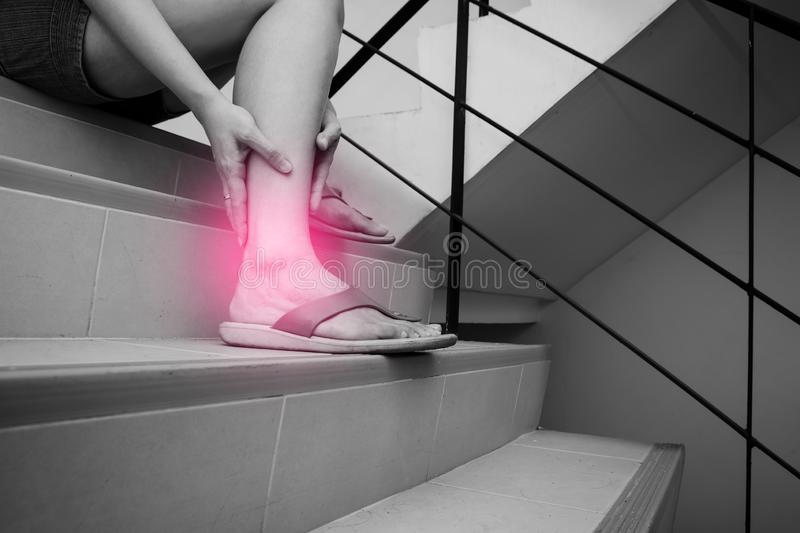 Woman has calf cramp and touching hurt leg during go down stairs. Black and white tone with red spot at her leg.  stock images