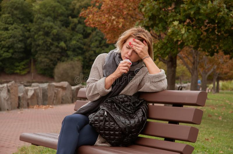 Woman has cold or flu. Cough. Girl sitting on bench in the park royalty free stock photography