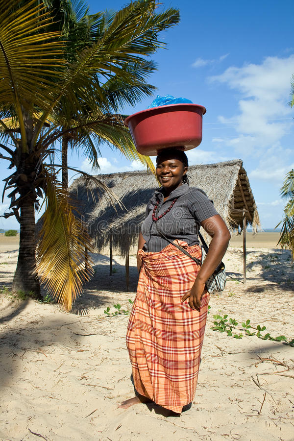 Woman has different goods in a bowl and carries it on her head traditionally. BARRA, MOZAMBIQUE - JUNE 13, 2015: Unidentified woman has different goods in a royalty free stock photography