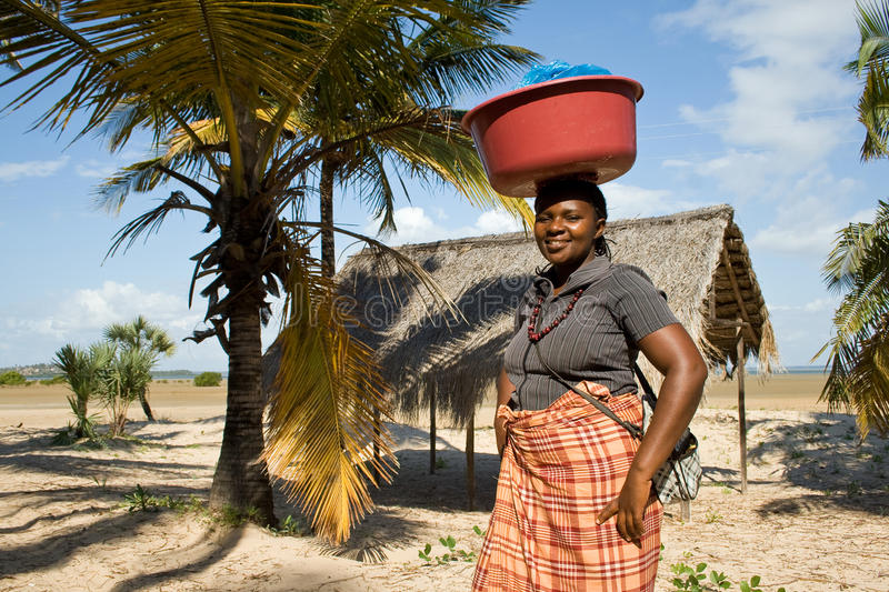 Woman has different goods in a bowl and carries it on her head traditionally. BARRA, MOZAMBIQUE - JUNE 13, 2015: Unidentified woman has different goods in a royalty free stock image