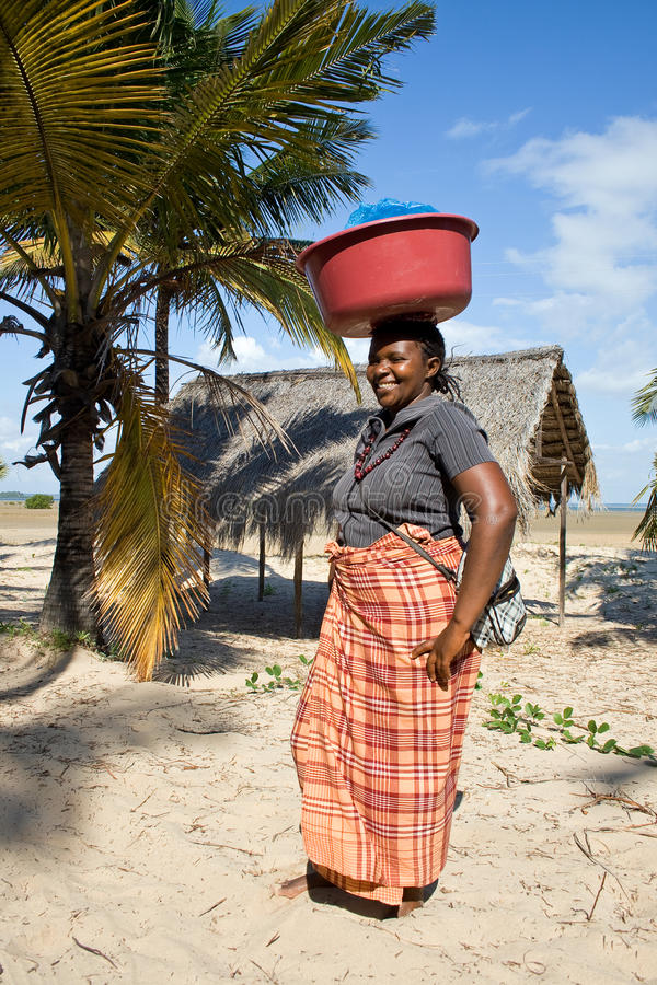 Woman has different goods in a bowl and carries it on her head traditionally. BARRA, MOZAMBIQUE - JUNE 13, 2015: Unidentified woman has different goods in a stock photos