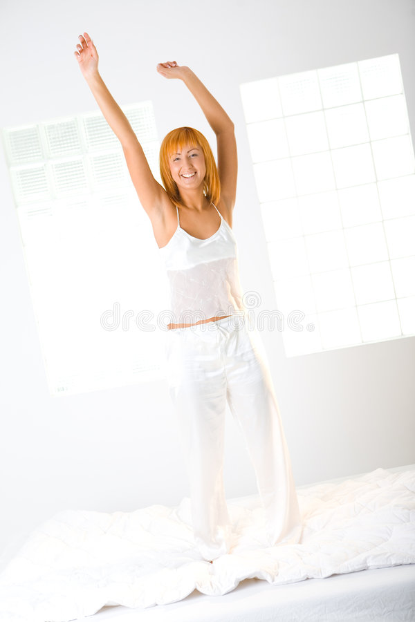 Woman has fun on bed royalty free stock photo