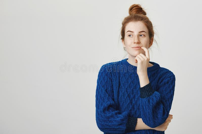 Woman has great plan in mind. Indoor shot of pretty woman with red hair and freckles in winter sweater holding finger on stock photos