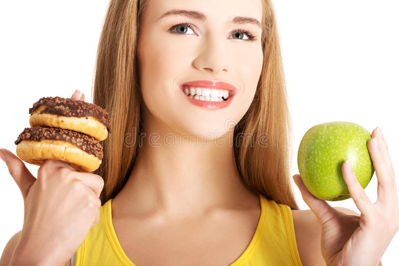 Woman has a hard choice between donut and apple stock images