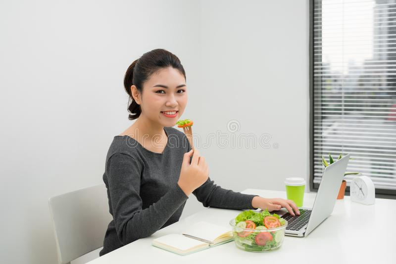 Woman has healthy business lunch in modern office interior. Young beautiful businesswoman at working place, eating vegetable. Salad in bowl, diet and vegetarian stock image