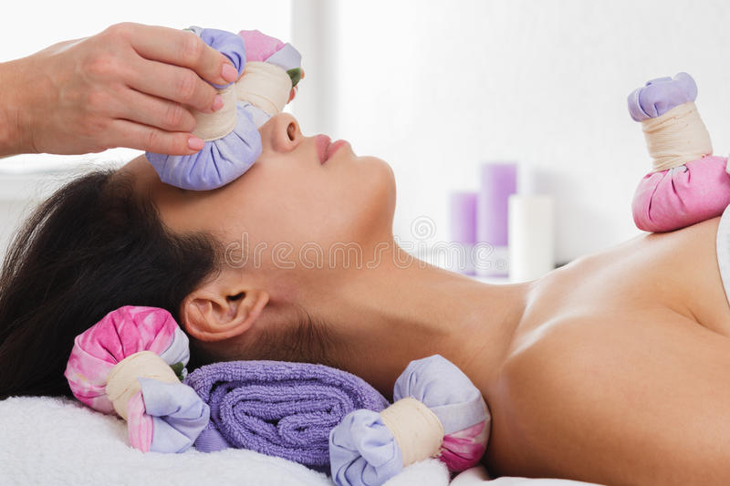 Woman has herbal ball massage in ayurveda spa wellness center. Herbal ball face massage in ayurveda spa. Female massagist with young woman in wellness center stock photo