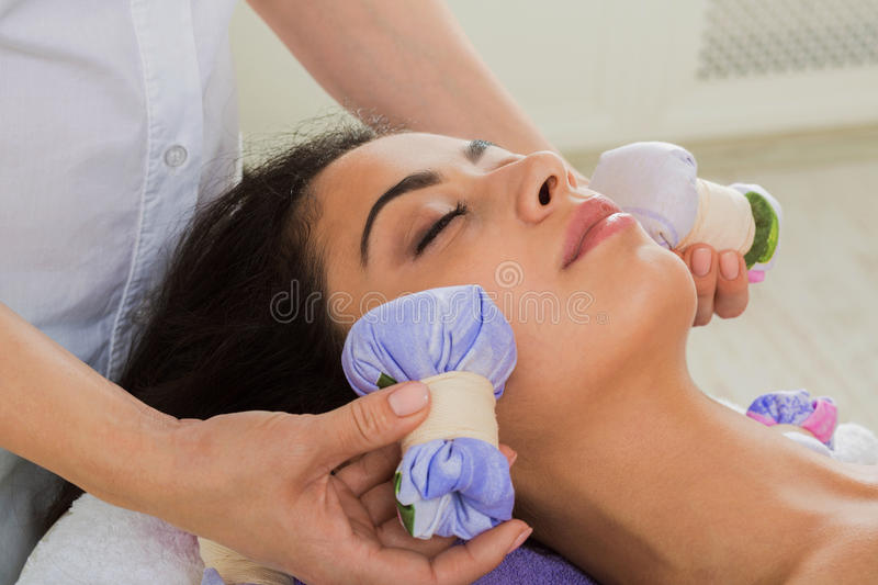 Woman has herbal ball massage in ayurveda spa wellness center. Herbal ball face massage in ayurveda spa. Female massagist with young woman in wellness center royalty free stock photos