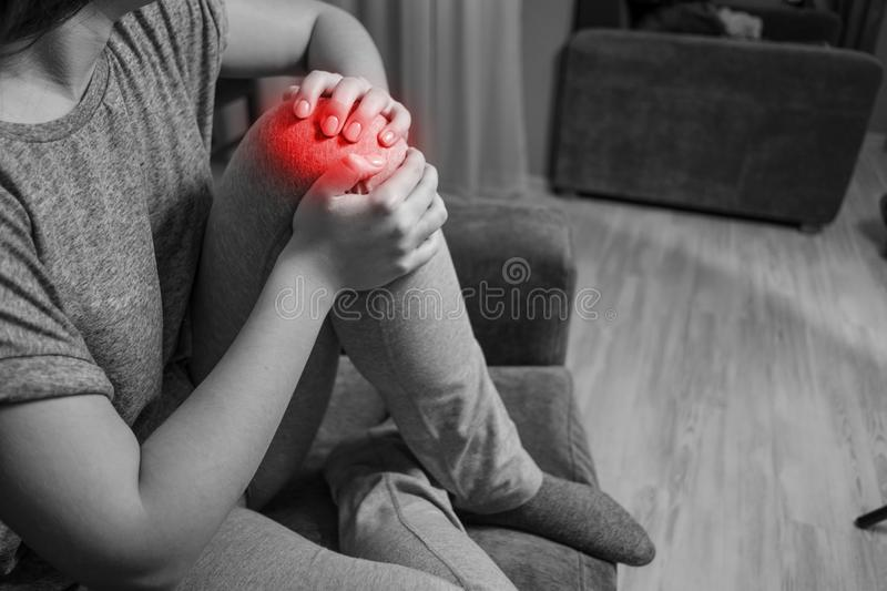 Woman has knee pain, black and white photo red accent, close up of pain. Young woman has knee pain, black and white photo red accent, close up of pain stock photography