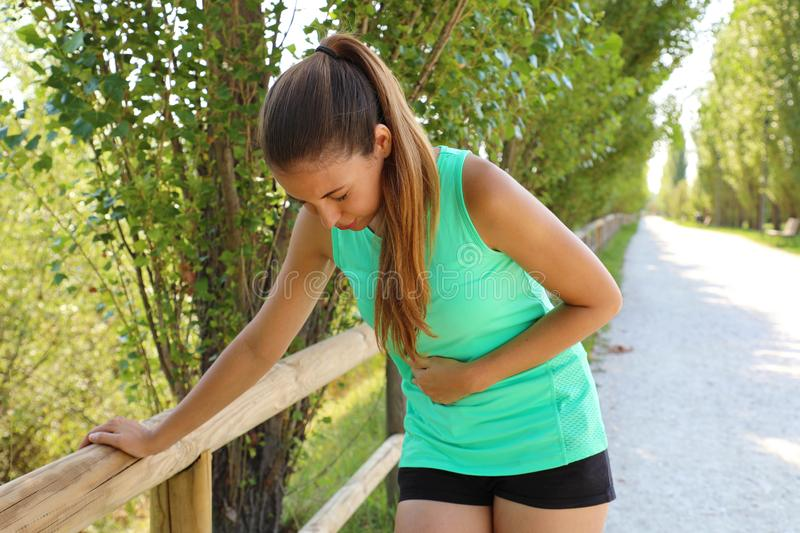 Woman has side cramp. Young woman suffering from abdominal pain while running outdoor stock images