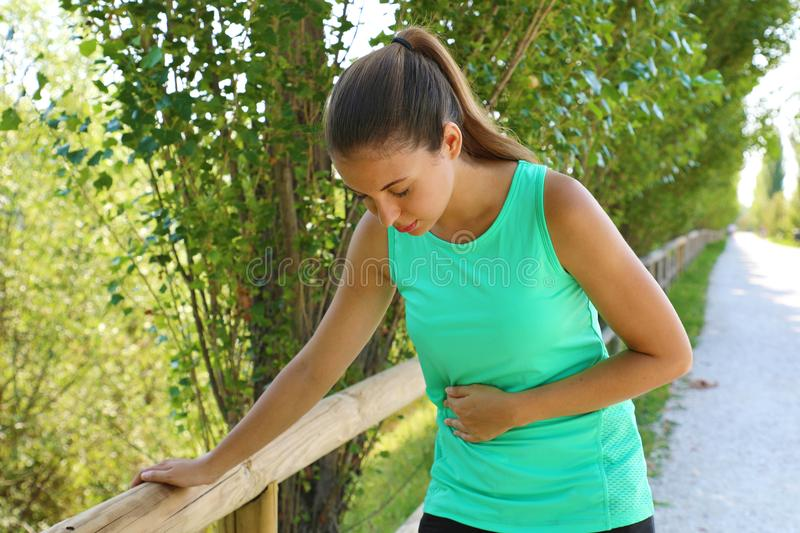 Woman has side cramp. Young woman suffering from abdominal pain while running outdoor stock photos