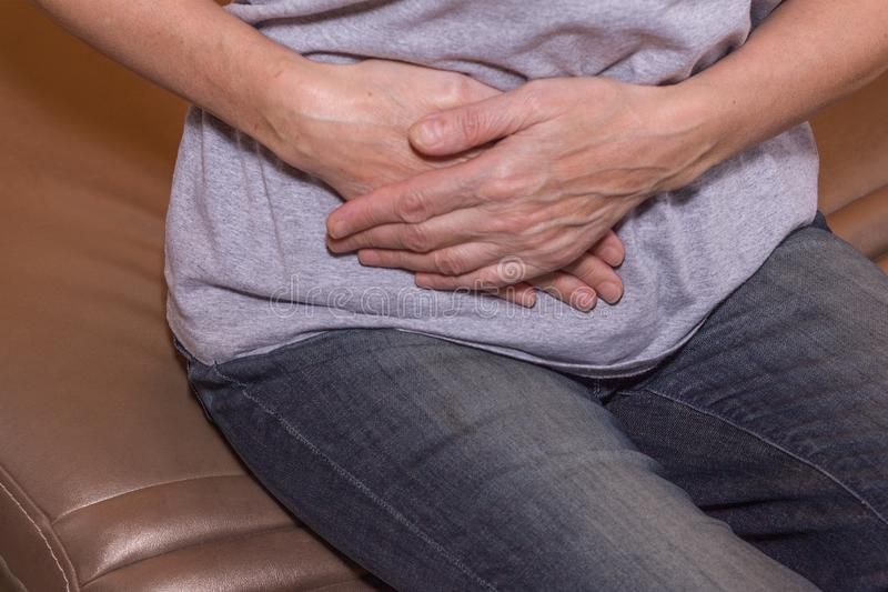 A woman has a stomach ache.  stock photo