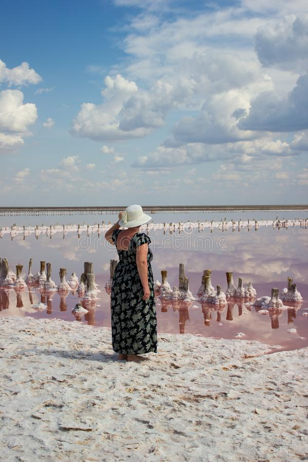 Woman in a hat on background of a salt-producing plant stock image