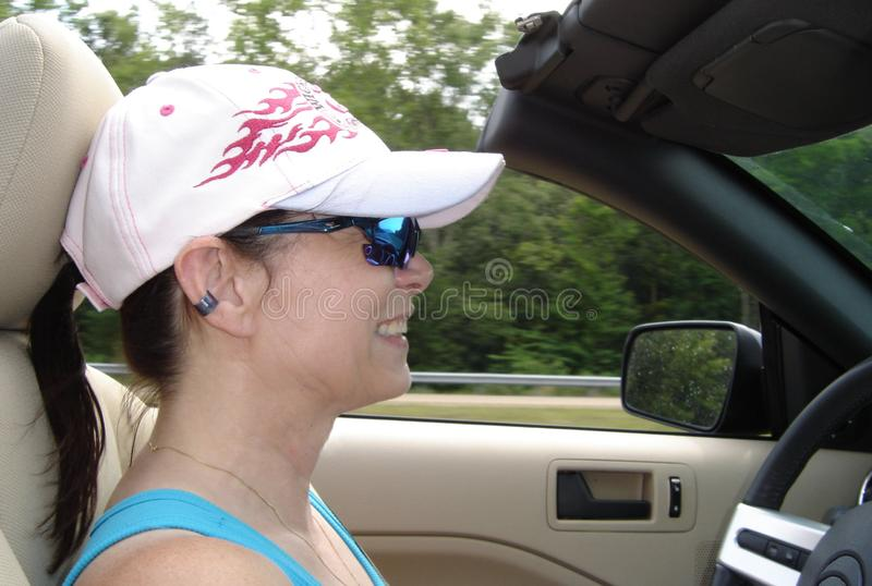 Woman in a hat driving a convertible. Woman in a pink ball cap enjoying driving in a convertible with its top down stock photo