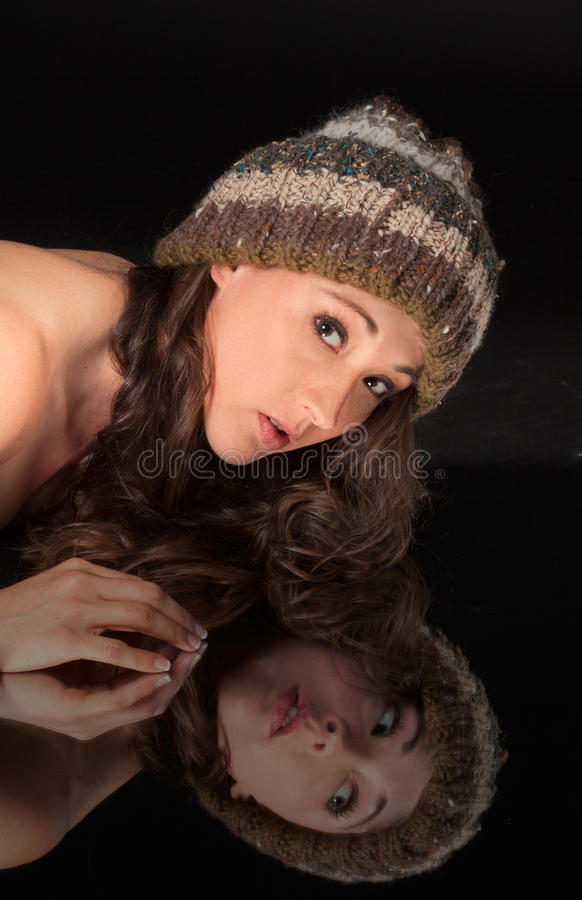 Woman in Hat Leaning Over Mirror royalty free stock photography