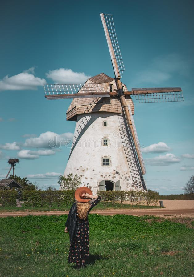 Woman in hat looking at old wildmill building, summer sunny day royalty free stock photography