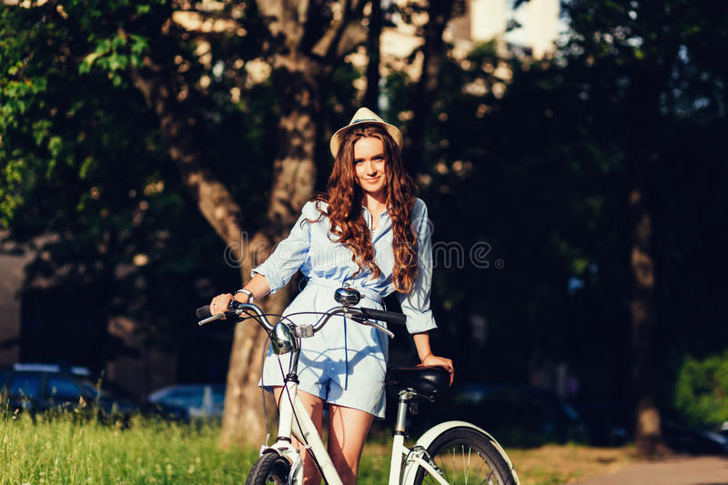 Woman in hat posing with bike stock images