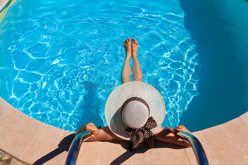 Woman in hat relaxing at the pool royalty free stock images