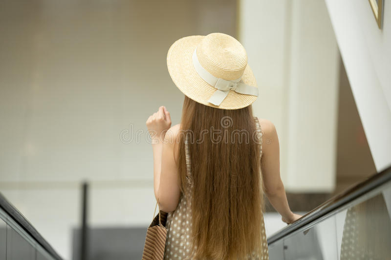 Woman in hat riding escalator in shopping mall. Young beautiful long-haired customer woman wearing a hat and cute polka dot summer dress carrying shopping paper stock photography