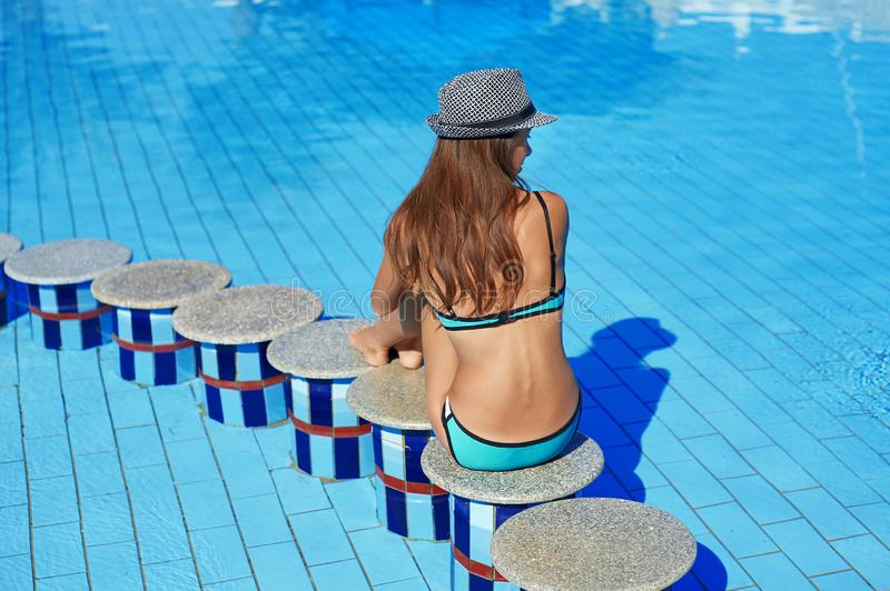 Woman in hat sits on the edge of stone in the middle of the swimming pool. Beautiful exotic hotel relax holiday.  royalty free stock image