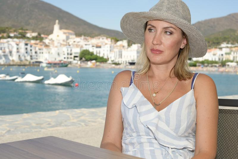A woman in a hat sitting on a terrace on the promenade of a well-known Mediterranean town called Cadaqués with the village in the stock photography