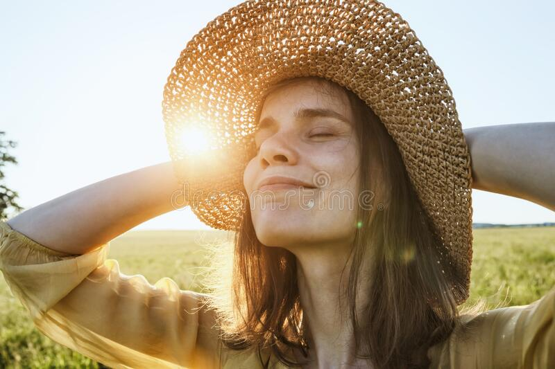 Woman with hat smiling and enjoying summer sunlght in meadow stock photos