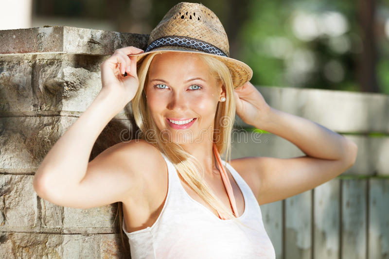 Woman with hat. Standing near fence on a sunny day stock image