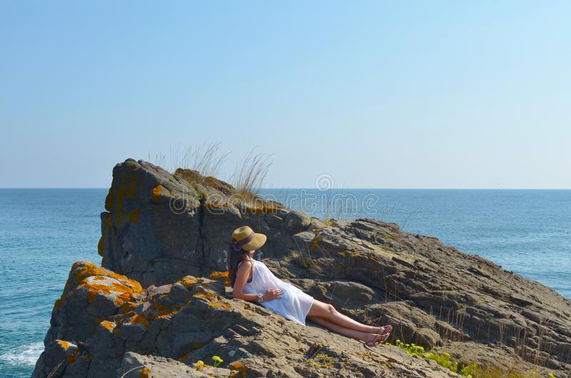 Young Woman Sitting on the Edge of a Rocks above the Sea stock images