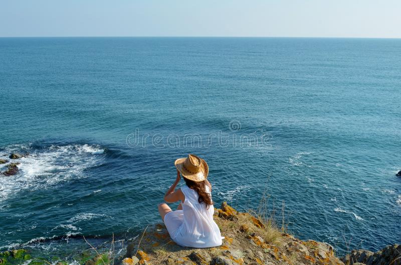 Young Woman Sitting on the Edge of a Rocks above the Sea stock photography