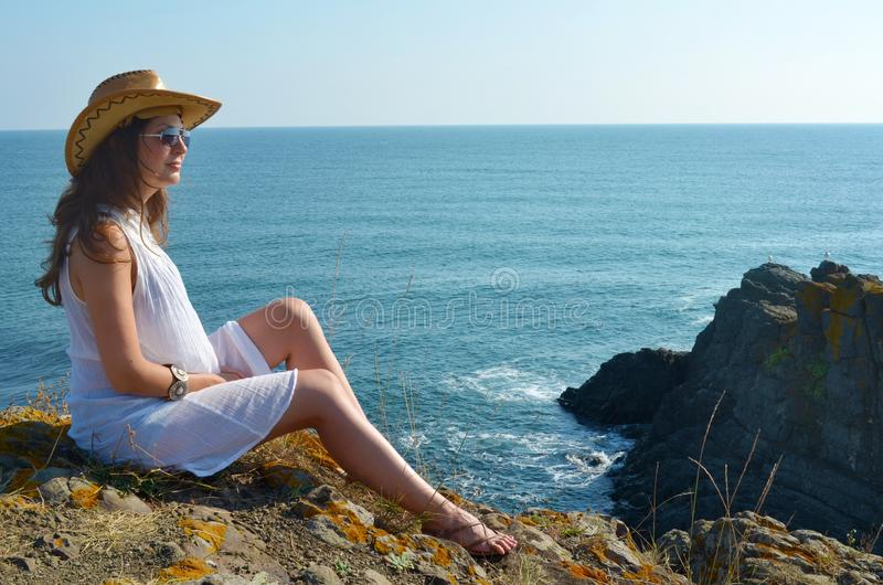 Young Woman Sitting on the Edge of a Rocks above the Sea royalty free stock photos