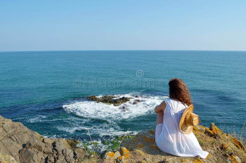 Young Woman Sitting on the Edge of a Rocks above the Sea royalty free stock photography