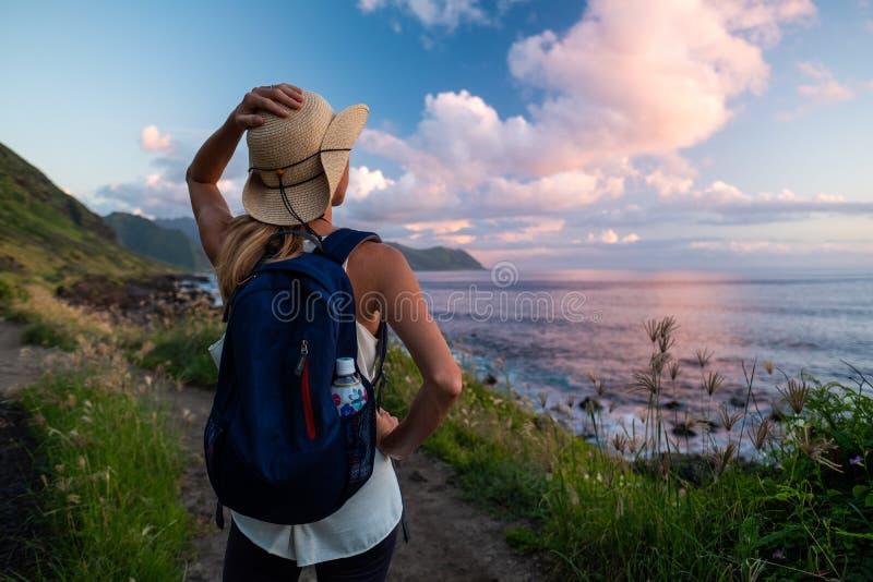 Woman in hat. Enjoys sunset coastal view royalty free stock photo