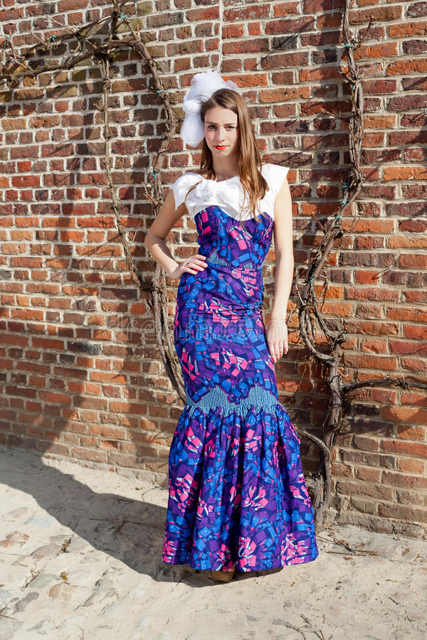 Woman haute couture dress. Woman in blue haute couture dress in front of a red brick stone wall with ivy standing in sandy ground stock photos