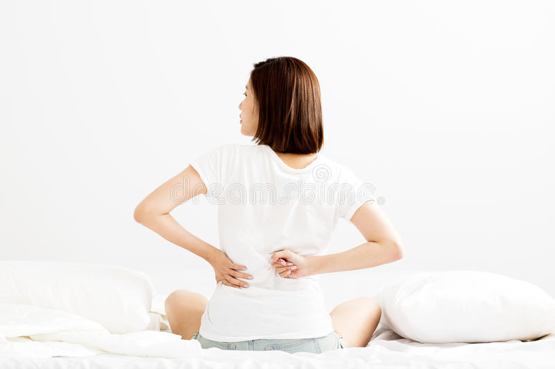 Woman have backache on white bed stock images