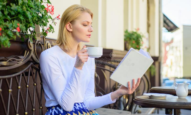 Woman have drink cafe terrace outdoors. Perfect morning concept. Girl drink coffee while read new bestseller book by stock photos