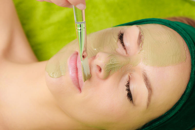 Woman having algae mud mask on face. Someone applying woman green algae mud mask on face. Beauty, relaxation, skincare, wellness in spa concept royalty free stock photos