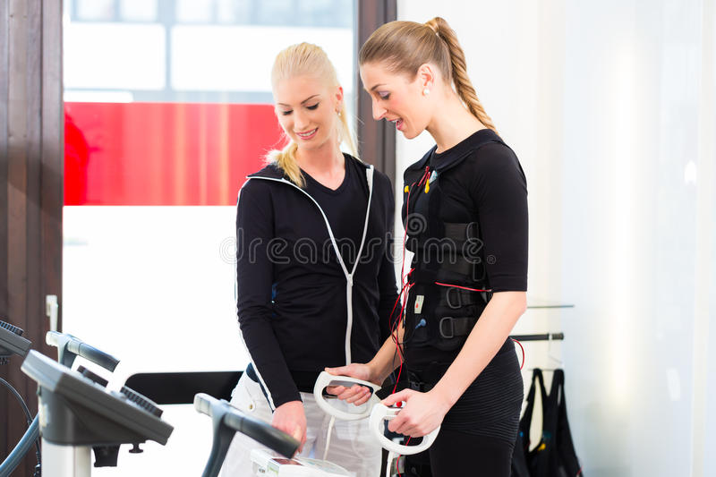 Woman having body fat measuring. Female coach controlling results after ems electro muscular stimulation training with body fat measuring stock photo