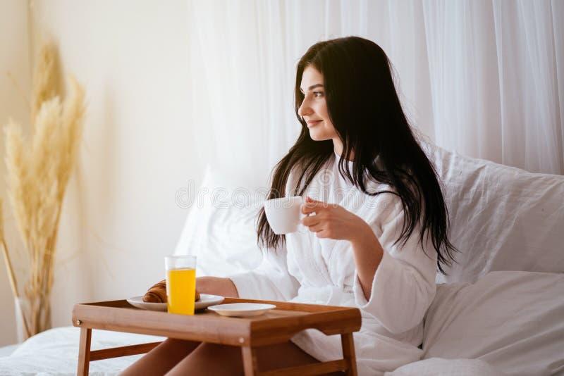 Woman having breakfast in bed in cozy hotel room royalty free stock image