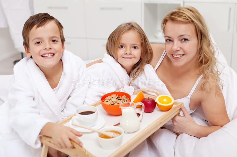 Woman having breakfast in bed with the kids. Morning family portrait royalty free stock image
