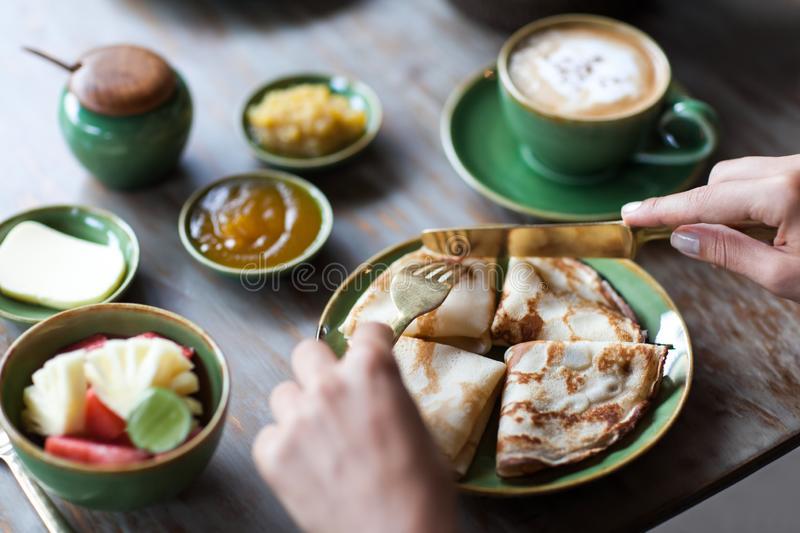 Woman having breakfast and cut crepes, cappuccino and homemade jams. Woman having breakfast and cut crepes, coffee and homemade jams royalty free stock images