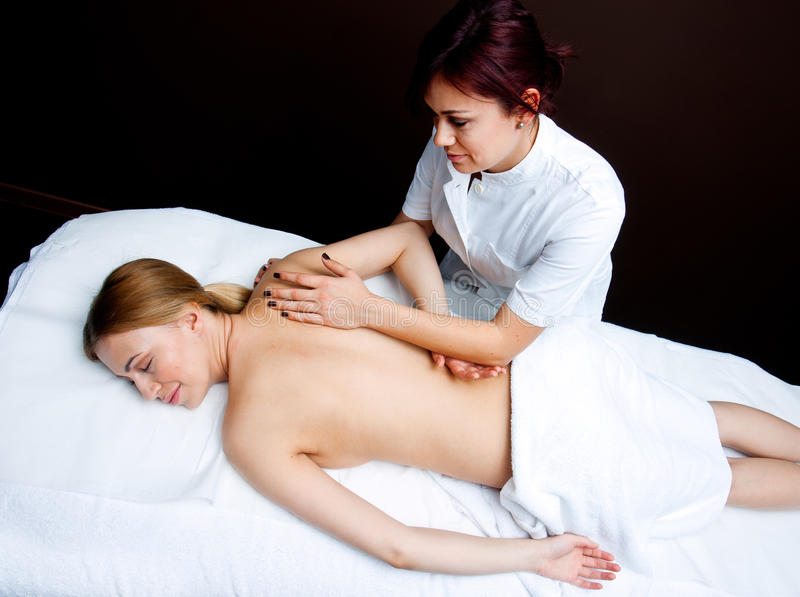 Woman having chiropractic back adjustment. Attractive women on massage table in beauty salon having chiropractic back adjustment stock photography