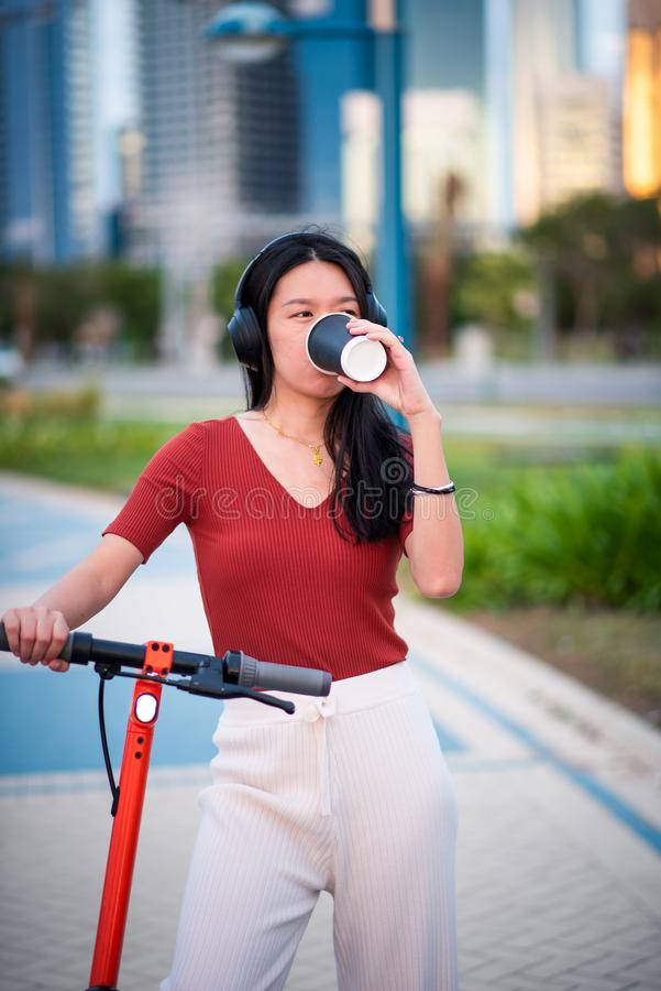 Woman having a coffee brake while using electric scooter stock photo