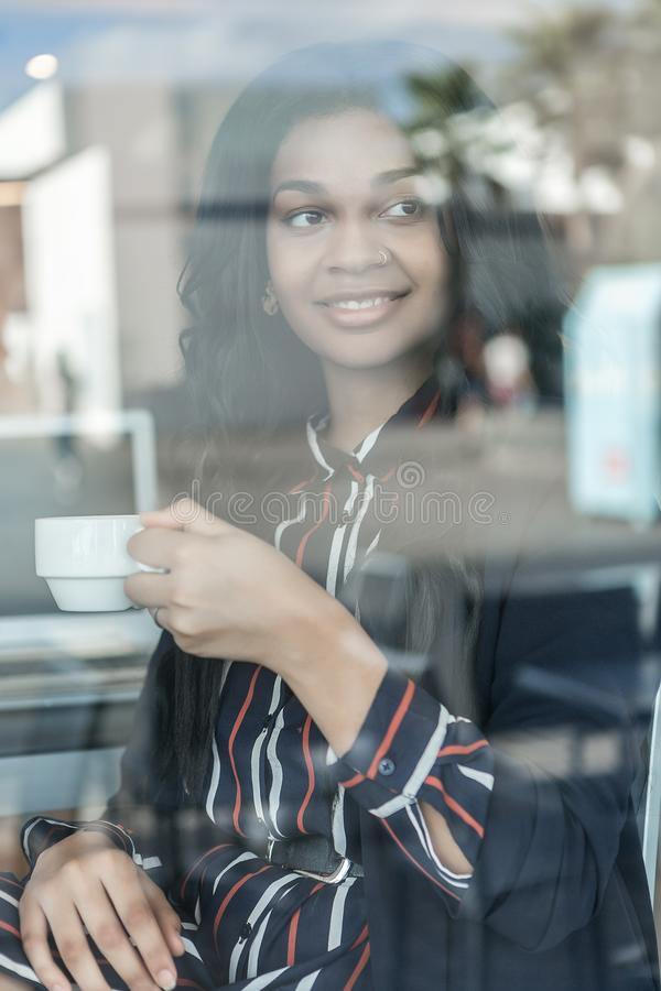 Woman having a coffee through the glass stock images