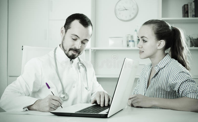 Woman having consultation with male doctor in hospital stock images